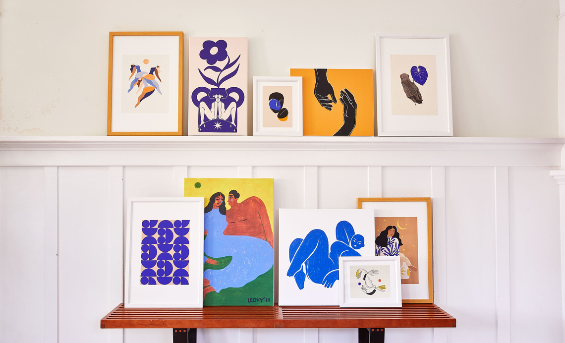 gallery wall of leaning framed prints and canvas prints in yellow, blue and white