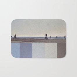 Two cyclists on the beach. Blue gray sea, sun, sky. Bath Mat