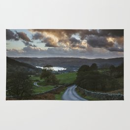 Steep mountain road 'the struggle' at sunset, with Lake Windermere beyond. Lake District, UK. Rug