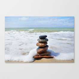 Stones in pyramid and wave on sand beach Canvas Print