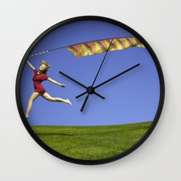 Freedom - A young girl jumping with a colorful kite banner on a clear blue sky day Wall Clock