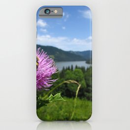 Bumblebee sitting on pink thistle, mountain lake scenery in the background blue sky iPhone Case