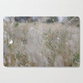 Tall wild grass growing in a meadow Cutting Board