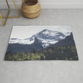 Winter and Spring - green trees and snowy mountains Rug