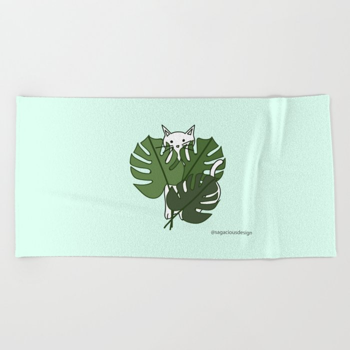 Cat hidden in the palm leaves Beach Towel