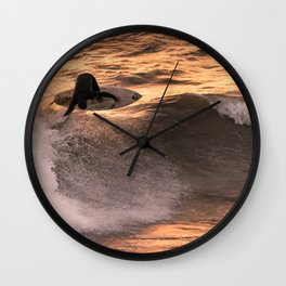 Surfer grabs air on wave at sunset Wall Clock