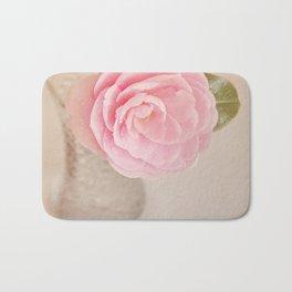 Single pink Camelia rose in clear vintage vase. Bath Mat