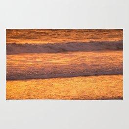 Surfer walking along beach at sunset Rug