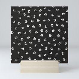 Doodle white paw print seamless fabric design pattern with black background Mini Art Print