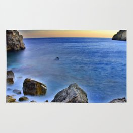 Beach at sunset with a rocks on the s Rug