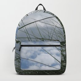 Grass in the dunes at sea against blue sky with white clouds Backpack