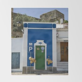 a small blue building by castle walls in an Alentejo street, Portugal Throw Blanket