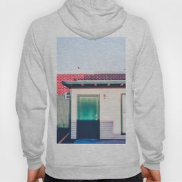 green wood building with brick building in the city Hoody