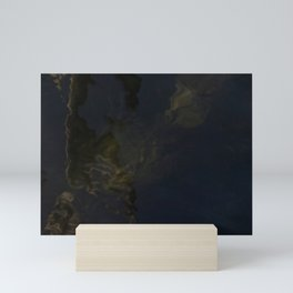 Water surface reflects the wooden pole together with surfacing algae. Mini Art Print