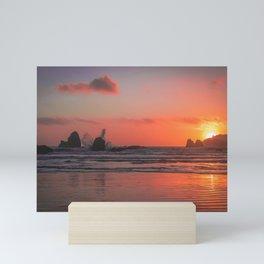 Waves crashing into rock at sunset Mini Art Print