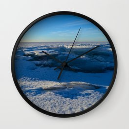 blue sky over the snowy ice space of the frozen Baltic Sea in a winter morning Wall Clock
