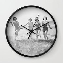 Four women run in water on the beach Wall Clock