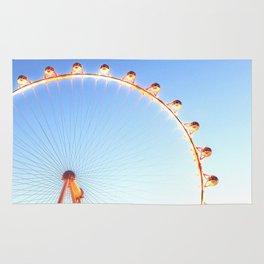 orange Ferris Wheel in the city with blue sky Rug