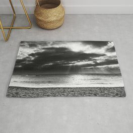 ray of sun over the beach at Kauai, Hawaii with cloudy sky in black and white Rug