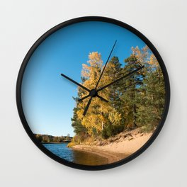 River with sandy shore with trees in autumn colors on a sunny day Wall Clock