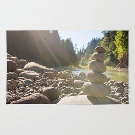 Cairn of stacked rocks along banks of Oregon river Rug
