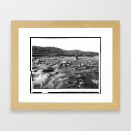 Man with rifle stands in mountain stream as it floods, east of Palmdale, California, ca.1920 Framed Art Print