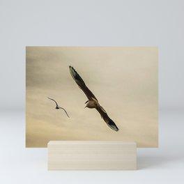 Seagulls flying on a beach Mini Art Print