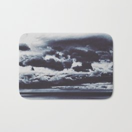 a boat sails alone at an abstract stormy cloudscape Bath Mat