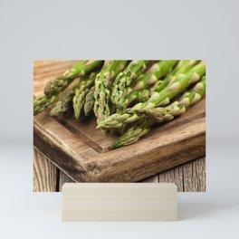 Fresh Asparagus on rustic wooden server board Mini Art Print