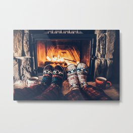 Feet in woollen socks by the Christmas fireplace. Couple sitting under the blanket, relaxes by warm fire and warming up their feet in woollen socks. Winter and Christmas holidays concept. Metal Print