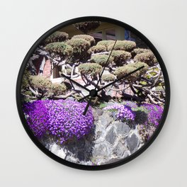 Rock Retaining Wall With Beautiful Trees and Purple Flowers Wall Clock