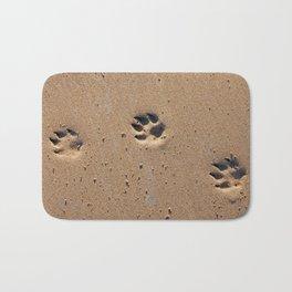 Dog paw prints on a sandy beach Bath Mat