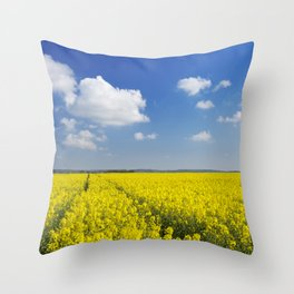 Path through blooming canola under a blue sky with clouds Throw Pillow