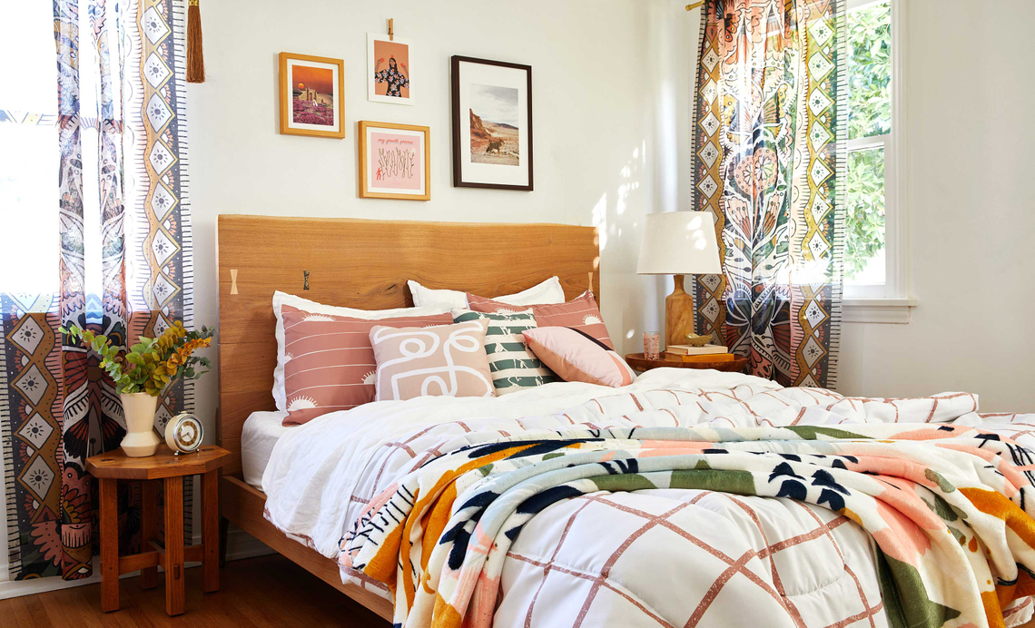 bedroom with pink brown and green comforter and pillows