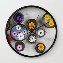 Colorful flowers floating in water in ceramic bowls on rustic wooden table.  Wall Clock