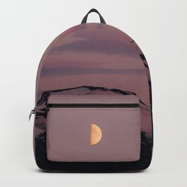 Moon on purple sky above icy volcano Backpack