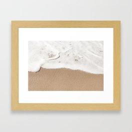 Wave gently washes up on a sandy beach Framed Art Print