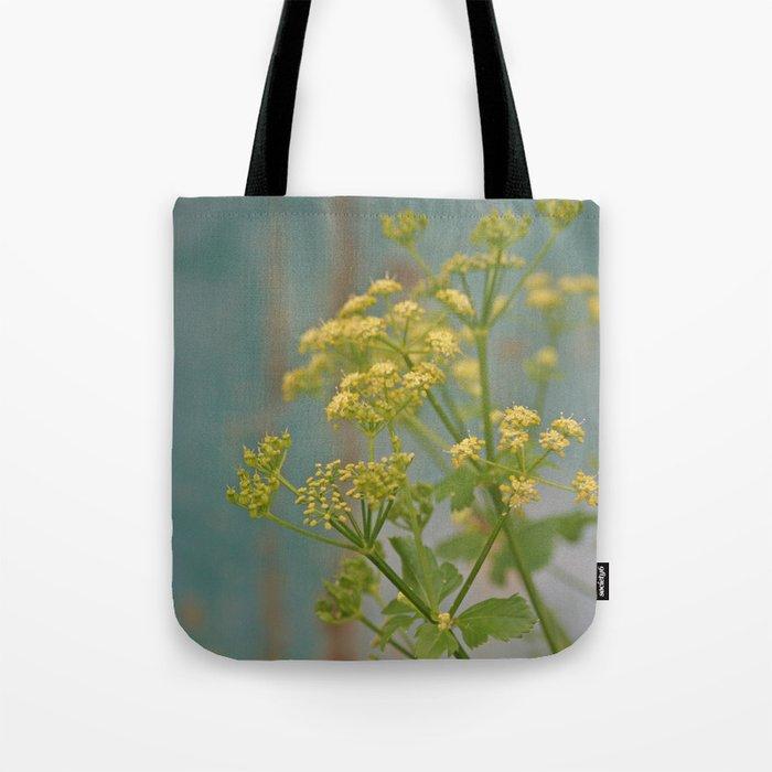 Yellow wildflowers on blue rusty metal Tote Bag