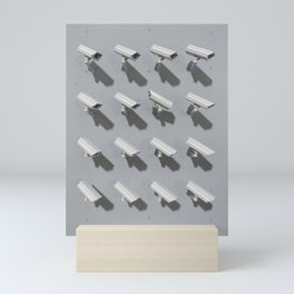 Group of cctv cameras pointing at the same direction except one Mini Art Print