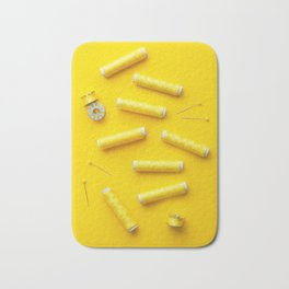 Colorful yellow thread spools over bright yellow background Bath Mat