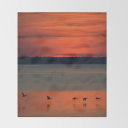 A flock of geese flying north across the calm evening waters of the bay Throw Blanket