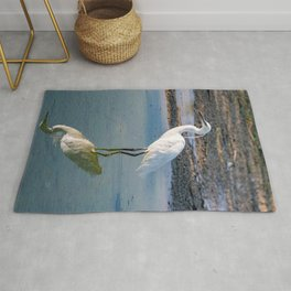 The image of a Little Egret reflected in the water of a pond Rug