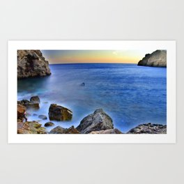 Beach at sunset with a rocks on the s Art Print
