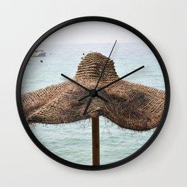 Beach umbrella in natural fibers on the shore of Lake Garda Wall Clock