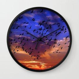 Flight of flamingos at sunset Wall Clock