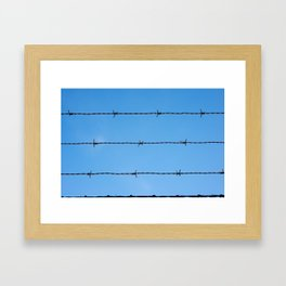 Contseptual shot of barbed wire over blue sky Framed Art Print