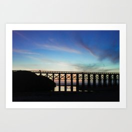 Couple watching the sunset while childeren play in the water underneath them Art Print