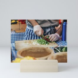 Cook chopping spring onion on a wooden cutting board Mini Art Print