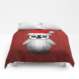 Baby Penguin Wearing a Santa Hat on Red Comforters