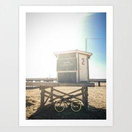 Bike leaning against lifeguard hut on beach Art Print